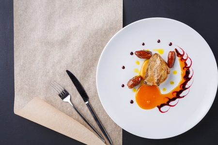 Roasted goose liver with date, apple and fruit and berry sauce painting with cutlery top view. Creative french cuisine, delicatessen restaurant meal Standard-Bild