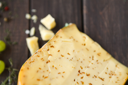 Gouda pesto cheese closeup. Still life on rustic wood background, copy space. Top view Stock Photo