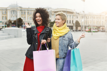 Happy girls with shopping bags outdoors. Smiling female friends in bright warm casual clothes having a city walk. Friendship, urban lifestyle and leisure concept