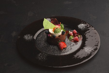 Exquisite restaurant mousse dessert. Chocolate and vanilla souffle on walnut biscuit served on glass plate finely decorated with fresh berries and mint. Exclusive meals and haute cuisine concept