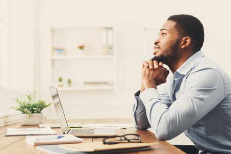 Pensive african-american businessman thinking about successful strategy, dreaming about something, copy space