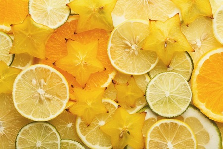 Citrus fruits slices abstract background. Green and yellow backdrop with cut lime, lemon, pomelo, kiwi and carambola stars. Closeup and texture, top view. Healthy eating, vitamins and veggie concept