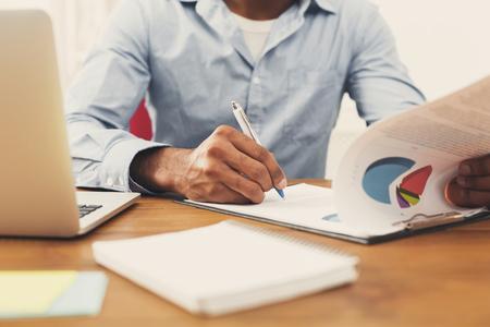 De zwarte documenten van de zakenmanlezing in modern wit bureau. Jonge onherkenbare Afro-Amerikaanse arbeider met papieren, kopie ruimte Stockfoto - 91965547