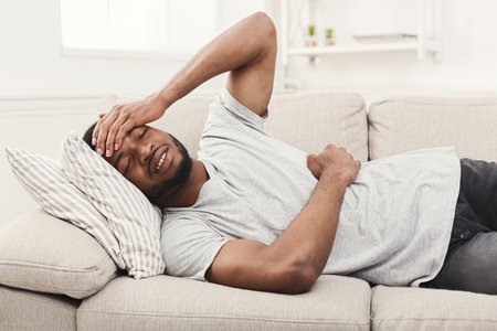 Handsome young african-american man suffering from stomachache and headache, while lying on sofa at home