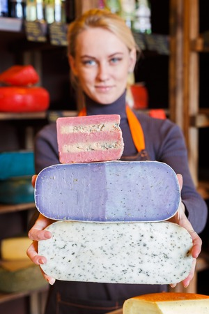 Female shop assistant suggesting different kinds of cheeses, grocery shop background