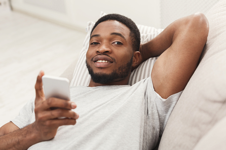 Young happy black man at home sending messages on smartphone lying on beige couch in light livingroom, copy space
