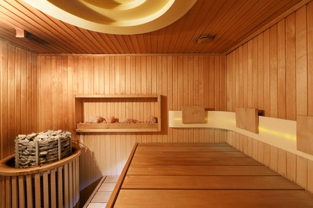 Interior of wooden sauna in hotel. Steam room in spa, ready for wellness procedures, copy space