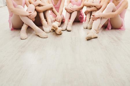 Little ballerinas talking in ballet studio. Group of girls having break in practice, sitting on floor, crop. Classical dance school 스톡 콘텐츠