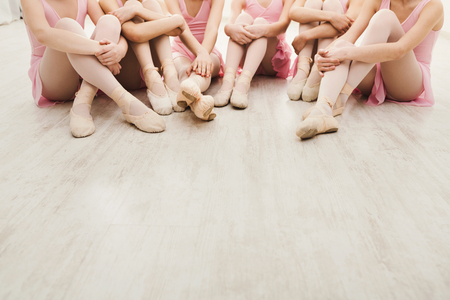 Little ballerinas talking in ballet studio. Group of girls having break in practice, sitting on floor, crop. Classical dance school Banco de Imagens