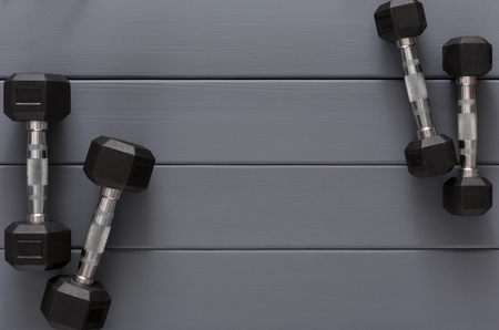 Dumbbells on grey wooden background top view copy space. Weight exercise, powerlifting, bodybuilding concept