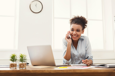 Happy smiling african-american business woman at work talking on phone and taking notes, sitting at her working place in office, copy space