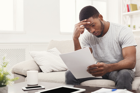 Young tired african-american man with paperwork. Student exhausted while preparing for tests. Guy having headache on sofa at home, copy space 版權商用圖片
