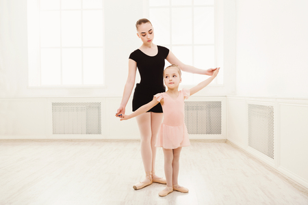 Little girl learning ballet with teacher copy space. Cute small ballerina training classical dance exercises with female coach.