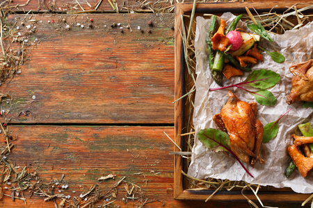 Excuisite restaurant food. Quails baked to golden crust with asparagus and chanterelles on grungy wooden platter on craft paper. Freshly cooked meals on rustic background with copy space, top view Stock Photo