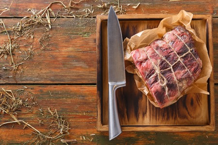 Raw black angus beef bound with rope in craft paper on cutting board. Aged prime marble meat and sharp chef knife at rustic wood background, top view, copy space Archivio Fotografico