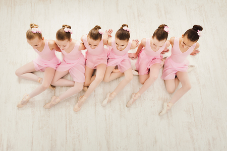 Petites filles dansent le ballet en studio. Jeunes ballerines qui s'étendent avant la performance, école de danse classique, espace copie, vue de dessus Banque d'images - 92103253