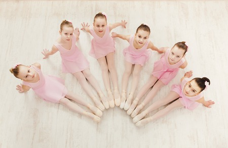 Little ballerinas in ballet studio, top view. Group of girls practicing position sitting on floor, classical dance studio
