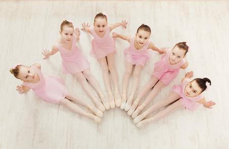 Kleine Ballerinen im Ballettstudio, Draufsicht. Gruppe Mädchen, welche die Position sitzt auf Boden, klassisches Tanzstudio übt