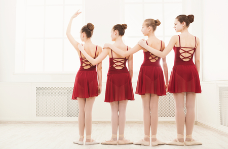 Young girls dancing ballet in studio. Choreographed dance by a group of graceful pretty young ballerinas practicing during class before performance. Classical dance school