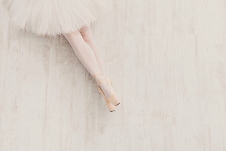 Young ballerina legs in pointe shoes at white wooden floor background, top view with copy space. Ballet practice, slim graceful feet of ballet dancer. Stock Photo