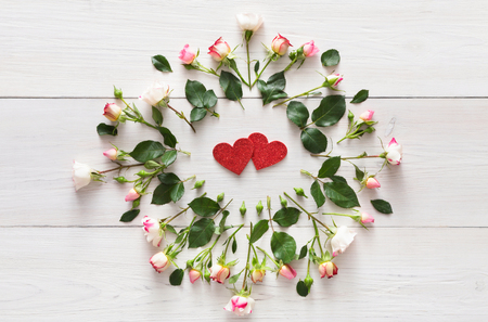 Valentine background with hearts and roses. Pale pink flowers framing paper love symbols on white rustic wood, copy space. Happy lovers day mockup, top view