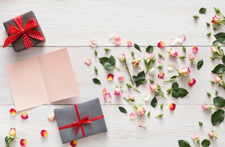 Pink rose flowers heart and handmade paper card with copy space, present boxes on white rustic wood. Happy lovers day mockup. Love or holiday concept