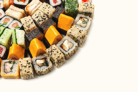 Sushi platter closeup isolated on white background. Japanese food restaurant delivery - maki, cheese and california rolls set placed in circle, copy space, mockup for menu Stock Photo