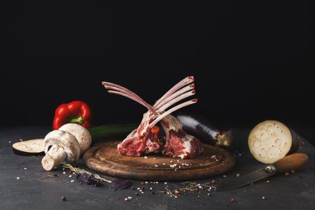 Rauw gesneden lamsrack. Vers vlees op houten bord op achterachtergrond. Organische ingrediënten voor restaurantmaaltijden, groenten, exemplaarruimte