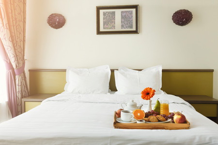 Breakfast served in bed on wooden tray with tea, juice, cookies, fruit and bright gerbera. Hotel room service, relax concept, copy space
