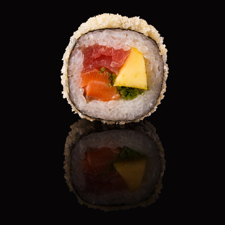 Sushi roll with fish, vegetables and cheese. Traditional japanese food on black glass with reflection, copy space. Asian restaurant meals delivery Stock Photo