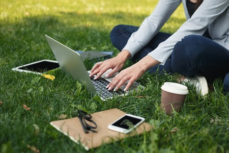 Young unrecognizable woman sitting outdoors on grass with laptop, typing, surfing internet, preparing for exams. Technology, communication, education and remote working concept, copy space