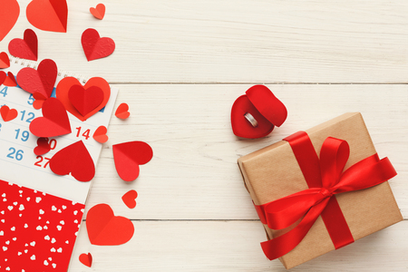Valentine background with red paper hearts border and gift box with copy space on white rustic wood. Happy lovers day present mockup