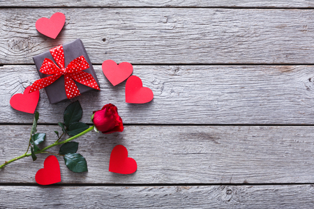 Valentine background with red rose flower, handmade paper hearts and present box on rustic wood, copy space. Valentine's Day, love, romantic concept. Horizontal orientation