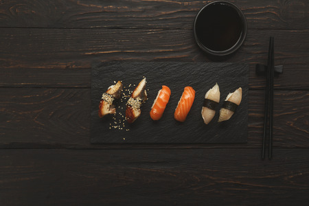 Colorful sushi platter in japanese restaurant, with chopsticks and soy sauce on dark wooden background, top view, flat lay, copy space