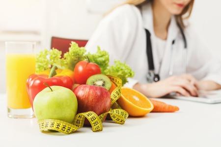 Ernährungswissenschaftlerschreibtisch mit gesunder Frucht, Saft und messendem Band. Ernährungsberater, der an Diätplan arbeitet. Gewichtsverlust und richtige Ernährung Konzept