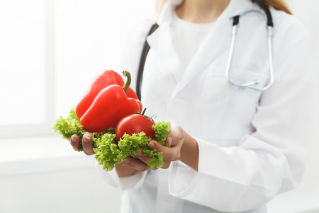 Unrecognizable nutritionist woman with lettuce, tomato and pepper at office, copy space. Healthy eating, right nutrition and slimming concept