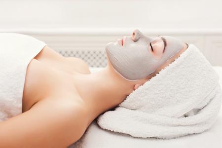 Mascarilla facial, tratamiento de belleza spa. Mujer aplicando máscara facial de arcilla en el salón de spa, cuidado de la piel, vista desde arriba, sobre la cabeza Foto de archivo