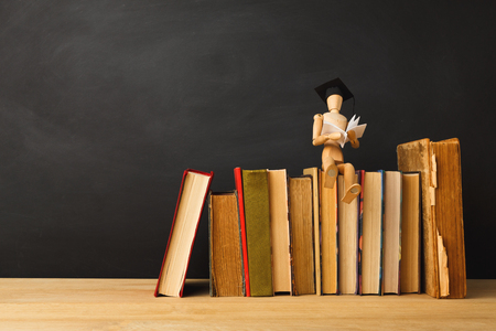 Educational background. Wooden marionette in graduation hat sitting on old books and reading against empty classroom blackboard for copy space. Back to school concept Stock Photo