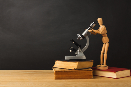 Educational background. Wooden marionette looking in microscope, standing on book against empty classroom blackboard for copy space. Back to school concept Stock Photo