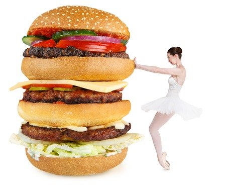Healhty lifestyle vs junk food conceptual background. Slim fit balerina rejecting huge burger isolated on white Stock Photo