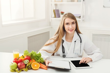 Female nutritionist working on digital tablet in office. Beautiful woman dietitian typing, counting calories or writing diet plan, copy space. Healthy eating concept Stock Photo