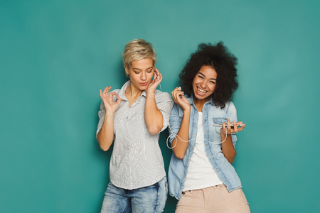 Two happy women listening music online on smartphone and sharing earphones sitting at blue studio background, copy space 版權商用圖片 - 93443421