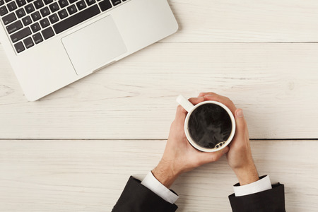 Mans hands holding coffee cup. Top view of human hands, coffee, laptop keyboard on white wooden table background. Education, business, technology concept Stockfoto