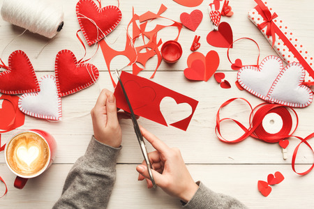 Valentines day diy - scrapbooking, wedding or other holiday decorations background. Handmade gift red heart creating, cut and paste , craft paper and tools on white wood. Above view, flat lay