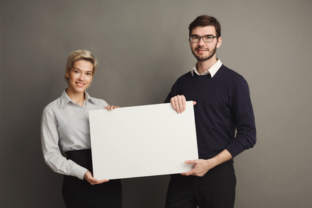 Happy young couple holding blank white banner with copy space on gray background
