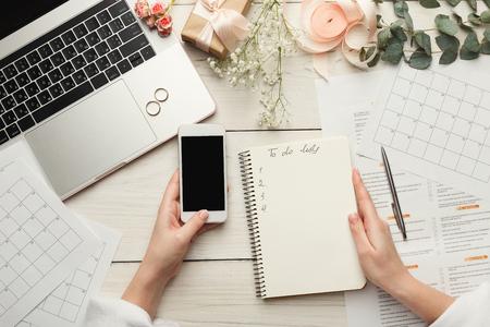 Hochzeitsarrangement Hintergrund. Weibliche Hände, die für Heirat, unter Verwendung des Laptops, des Smartphone, der Papierkalender und der Planer, Draufsicht sich vorbereiten. Brauttapete mit Exemplarplatz ein, zum der Liste zu tun Standard-Bild