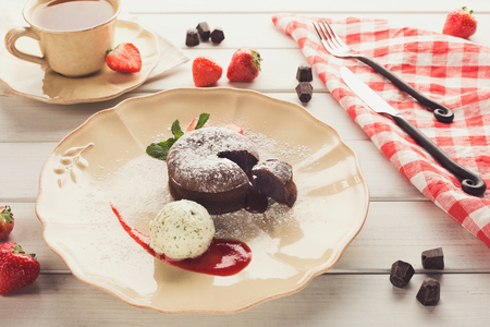 Cut chocolate fondant served with vanilla ice cream and strawberry on classic porcelain plate Stock fotó
