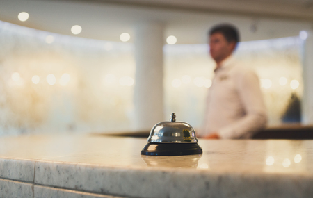 Hotel accommodation call bell on reception desk, contemporary interior, blurred man guest on background, copy space Stock Photo