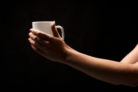 Female hands holding white coffee cup at black isolated background. Bar, hot beverages and morning coffee concept, copy space, cutout, low key Stock Photo