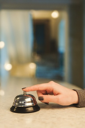 Woman ringing hotel service bell to attract attention in modern hotel, blurred background, copy space